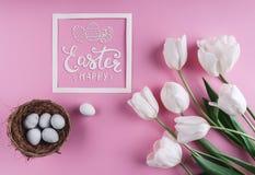 在巢的复活节彩蛋和在桃红色背景的白色郁金香花与复活节卡片 库存照片
