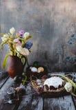 在巢的复活节蛋糕用复活节彩蛋和春天在水罐开花 免版税图库摄影