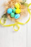 在巢的复活节彩蛋在土气白色背景 库存图片