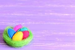 在巢的复活节彩蛋感觉在绿色西沙尔麻巢设置的复活节彩蛋隔绝在与copyspace的紫色木背景文本的 库存照片