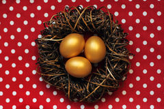 在巢的愉快的复活节金黄鸡蛋在红色圆点背景  免版税库存图片
