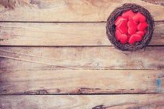 在巢的红色心脏在与空间的木背景 免版税图库摄影