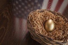 在巢的金黄鸡蛋与在表上的美国国旗反射 库存照片