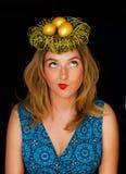 在巢的金黄鸡蛋在妇女的头 免版税库存照片