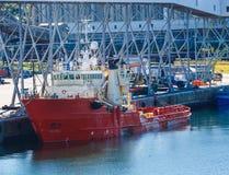 在工业口岸的橙色运转的船 免版税库存图片