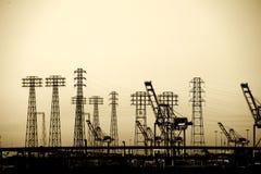 在工业口岸的电定向塔 库存照片