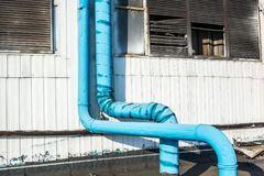 在工业墙壁上的蓝色管子 库存照片