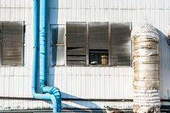 在工业墙壁上的蓝色管子 免版税库存图片