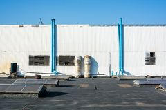 在工业墙壁上的蓝色管子 免版税库存照片