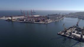 在工业贸易港上的飞行与容器和举的起重机在海堤防反对天空蔚蓝和发光 股票视频