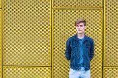 在工业黄色背景认为的时髦的青少年的男孩 免版税库存图片