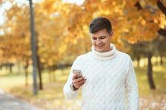 在工休期间的年轻英俊的人走在秋天公园和使用智能手机的 图库摄影
