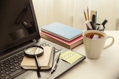 在工作书桌上的膝上型计算机,对键盘是与词质量的被胶合的贴纸 背景白色书桌,放大器,笔记薄,杯子  免版税库存照片