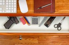 在工作书桌的个人武器 免版税库存图片