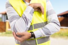 在工作伤害以后的建设者或建造者遭受的手肘痛苦 图库摄影