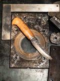 在工作凳的伪造的刀子在温暖的光 免版税库存图片