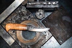 在工作凳的伪造的刀子在蓝色光 免版税库存图片
