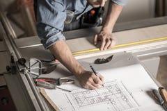 在工作凳的工匠的手 库存图片