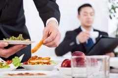 在工作午餐期间的亚裔人 免版税库存照片