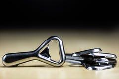 在工作台面的简单的金属片开启者在餐馆 一把银色和光亮的瓶盖启子 免版税图库摄影