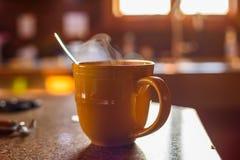 在工作台面的通入蒸汽的热的饮料在清早光 库存图片