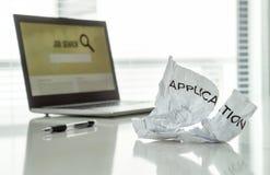 在工作和失望概念外面 在家庭办公室桌上的被剥去的工作申请书纸与膝上型计算机和就业搜索引擎 免版税库存照片
