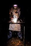 在工作和飞行火花的焊工 库存照片