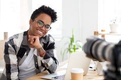 在工作场所的微笑的黑千福年的妇女射击 免版税库存图片