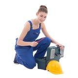在工作服的年轻有吸引力的妇女建造者与被隔绝的工具箱 免版税库存照片