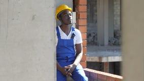 在工作期间,年轻美国黑人的建筑工人休假 库存照片