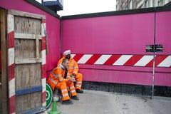 在工作期间的一个断裂 基于桃红色背景墙壁的橙色长袍的工作者 库存图片