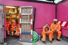 在工作期间的一个断裂 基于桃红色背景墙壁的橙色长袍的工作者 免版税库存图片