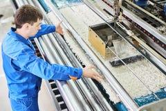 在工作的洗衣店工作者在地毯洗涤物的自动机器过程中 图库摄影
