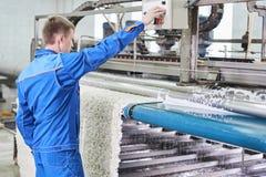 在工作的洗衣店工作者在地毯洗涤物的自动机器过程中 免版税库存照片