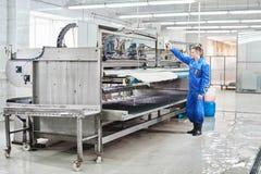 在工作的洗衣店工作者在洗涤的自动机器过程中地毯 免版税库存照片