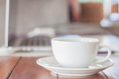 在工作站的加奶咖啡杯子 免版税库存图片