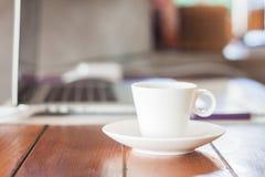 在工作站的微型加奶咖啡杯子 免版税库存照片