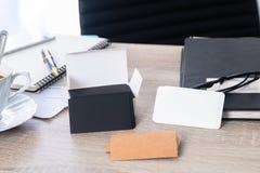 在工作者桌上的空白的公司本体名片包裹 库存图片
