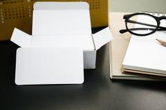 在工作者桌上的空白的公司本体名片包裹 免版税库存照片