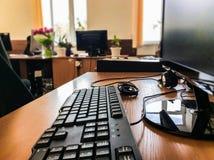 在工作表上的键盘与在被弄脏的背景的显示器 免版税图库摄影