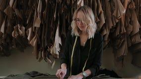 在工作过程中的时髦的裁缝金发碧眼的女人在一个缝合的演播室 股票录像