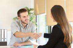 在工作面试以后的雇员和上司握手 免版税图库摄影