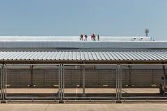 在工厂屋顶的工作者绘画  免版税库存图片