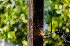 在工厂焊接金属的焊工在建造场所 图库摄影