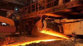 在工厂的高热金属生产,冶金学概念 储蓄英尺长度 流动在冶金滑道的溶解的钢 免版税库存照片