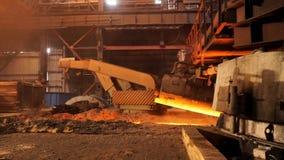 在工厂的高热金属生产,冶金学概念 储蓄英尺长度 流动在冶金滑道的溶解的钢 库存照片