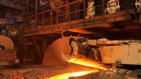 在工厂的高热金属生产,冶金学概念 储蓄英尺长度 流动在冶金滑道的溶解的钢 库存图片