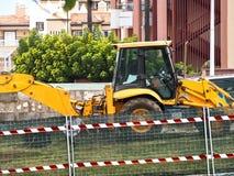 在工地工作的大黄色挖掘机 免版税库存照片
