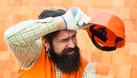 在工地工作的辛苦 重的行业 男性建造者抹从眉头的汗水 疲乏的建造者 物理工作 免版税库存图片