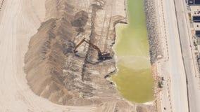 在工地工作,沙漠的挖掘机机械在背景中 加速的录影看法 股票录像
